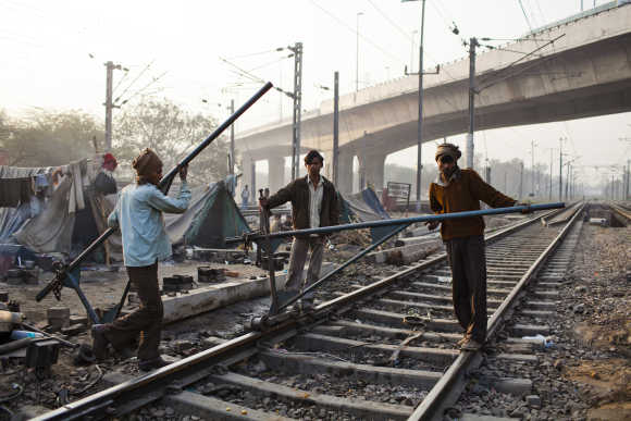 Labourers work on the tracks at Nizamuddin Railway Station.