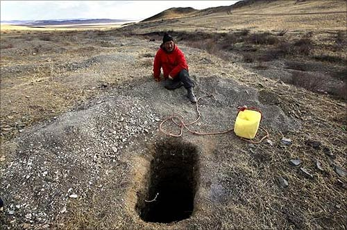 A small-scale miner rests next to a 15-feet (4.6-metre) deep hole he dug searching for gold on a small hill overlooking grasslands located around 200 km (125 miles) south-west of the Mongolian capital city Ulan Bator.