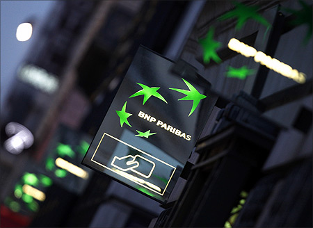 Illuminated signs light up at twilight outside the headquarters of the BNP Paribas bank in Paris.