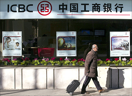 A man carries a case as he walks past the new branch of China's Industrial and Commercial Bank of China (ICBC) in central Madrid.