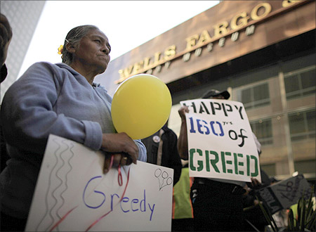 Elena Ruiz, 50 holds a sign during a march outside Wells Fargo to protest foreclosures in Los Angeles, California.