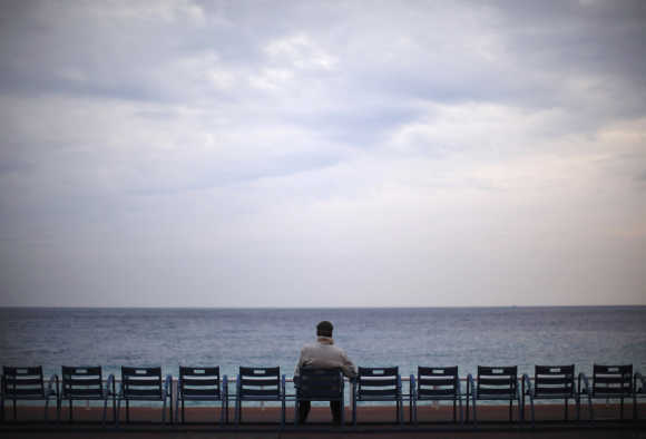 A man sits and looks out to sea on Promenade des Anglais in Nice, France.