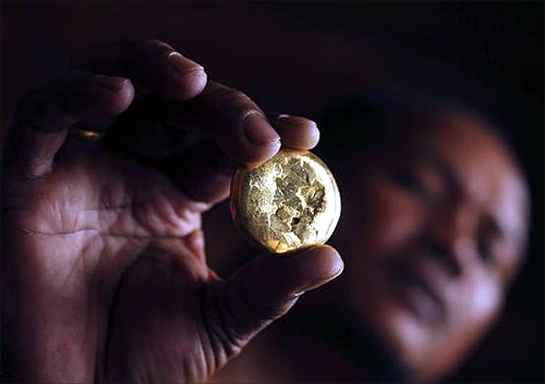 A local gold trader shows a piece of gold after he purchased it from a gold miner at the mine site in Poboya in Indonesia, Central Sulawesi province.