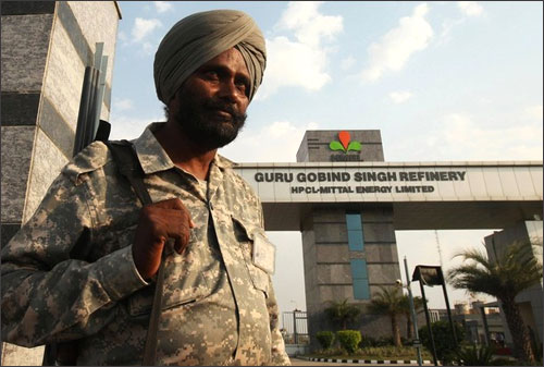 A security personnel stands guard in front of the main entrance of the Guru Gobind Singh oil refinery.