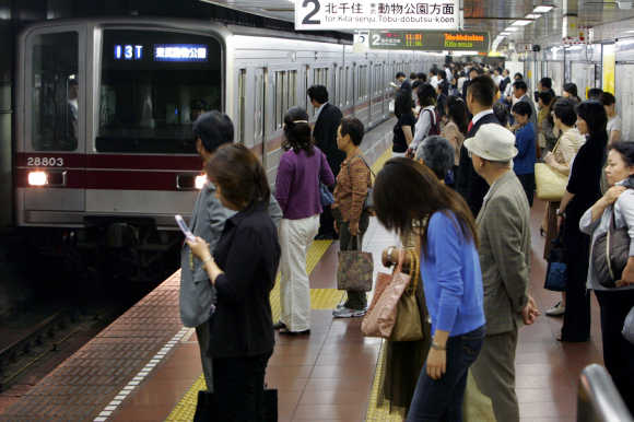 Passengers wait for a train on a platform at Tokyo Metro's Hibiya station.