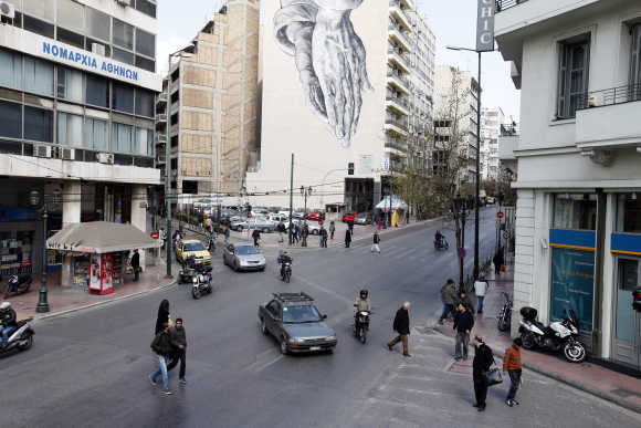 A mural of praying hands is displayed on the side of a hotel in central Athens.