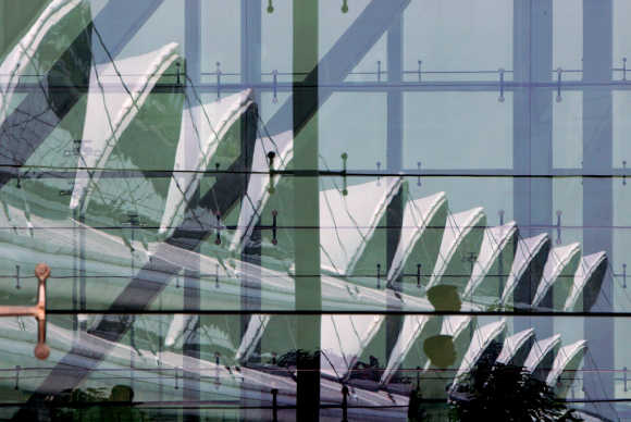 A man walks past a reflection of Guangzhou Baiyun International Airport's passenger terminal.