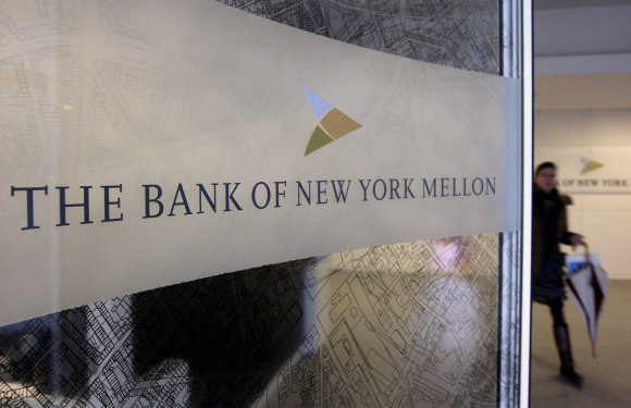 A woman walks past a logo at the office of the Bank of New York Mellon in Brussels.