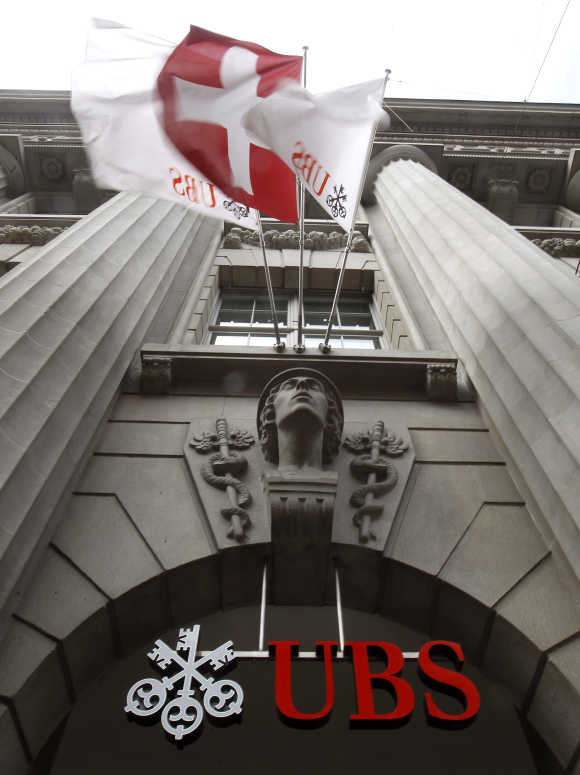 A Switzerland national flag flies over the logo of Swiss bank UBS at a branch office in Zurich.