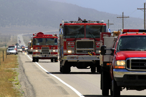 A line of fire trucks make their way down US highway 89 toward the Wood Hollow Fire north of  Fairview, Utah.