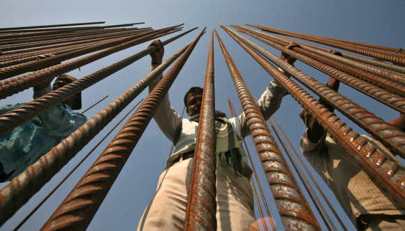 Workers hold iron rods at a construction site of a bridge on the river Tawi in Jammu.