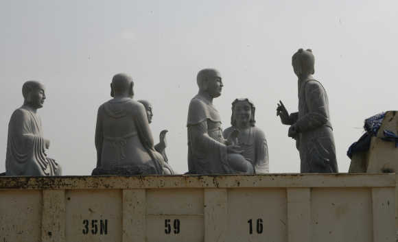 Stone statues of Buddhist arhats sit on a truck in Vietnam's northern Ninh Binh province.