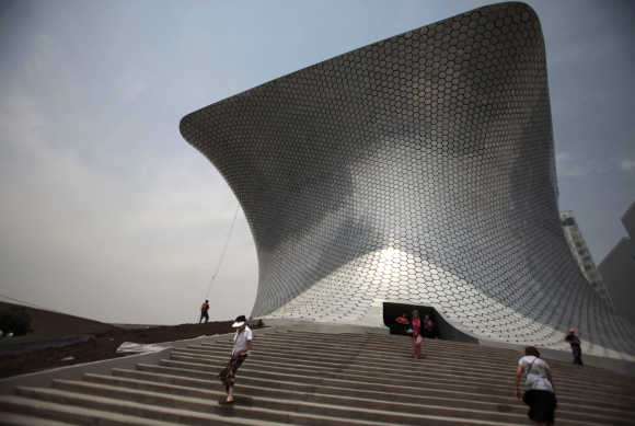 People walk outside the Soumaya Museum in Mexico City.