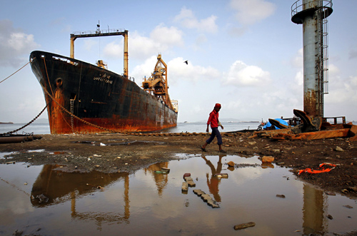 A man walks past a ship docked at a ship breaking yard in Mumbai.