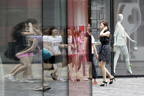 Pedestrians walk past a clothing store in Beijing's Sanlitun Area.