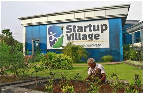 A gardener plants seedlings at the entrance of Start-up Village in Kinfra High Tech Park in Kochi.