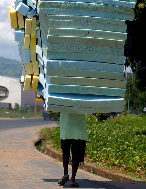 A Burundian villager carries a hip of mattresses for sell in the streets of capital Bujumbura.
