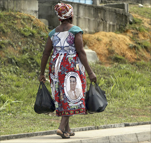 A woman with a picture of Equatorial Guinea's President Teodoro Obiang Nguema Mbasogo on her clothes walks along a street in Bata.