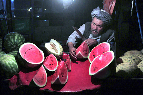 An Afghan man sells watermelons on his cart along a street as he waits for customers at the old part of Kabul.