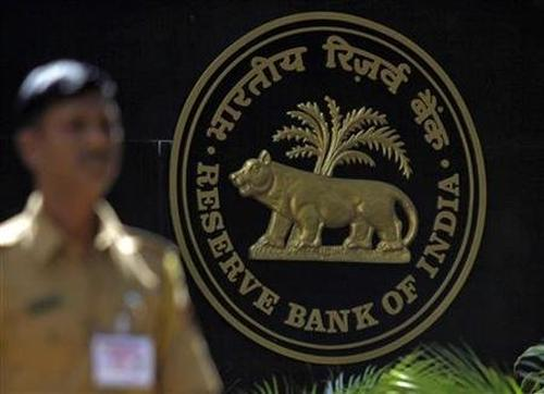 A policeman walks past the logo of the Reserve Bank of India (RBI) outside its head office in Mumbai