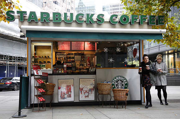 Customers leave a Starbucks coffee kiosk in the financial district of the City of London.