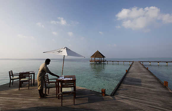 A waiter prepares the table at a restaurant on an island in Maldives.