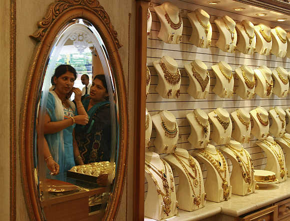 A woman is reflected in a mirror as she tries a gold earring inside a gold jewellery showroom in Kochi.