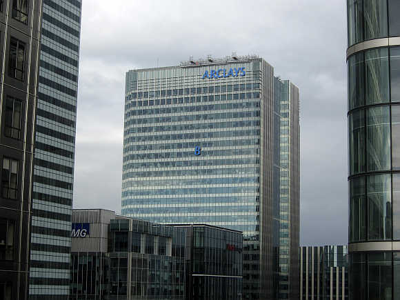 The letter 'B' of the signage on the Barclays headquarters in Canary Wharf is hoisted up the side of the building in London.