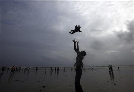 A man plays with his child on a beach in Mumbai.