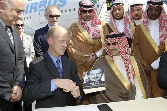 Chairman of Kingdom Holding Company Prince Alwaleed bin Talal gives a signed copy of his autobiography to Airbus President and CEO Tom Enders in Dubai.