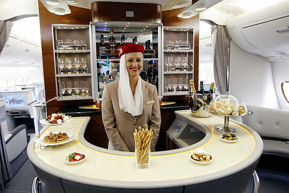 Flight attendant poses at bar in Business-Class section of Emirates' Airbus A380 in New York.