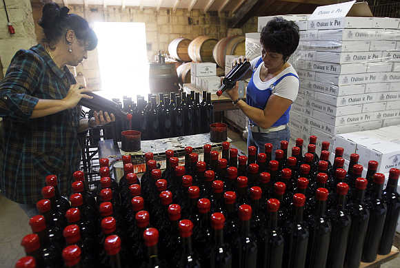 Employees close bottles of wine in the cellar of Chateau Le Puy in Saint Cibard, France.