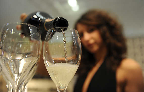 A woman fills glasses with sparkling wine in Verona, Italy.