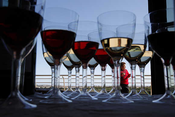A woman attends the Vivanda Taste the Med food festival as glasses of red and white wine are placed on a display table at Ta' Qali outside Valletta, Malta.