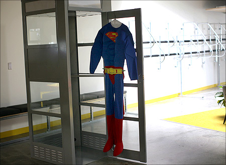 A superman costume hangs at a telephone booth for private cell phone discussions at the new headquarters of Facebook in Menlo Park, California.