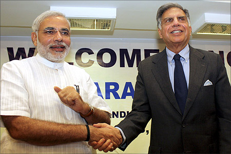 Chairman of Tata group Ratan Tata (R) shakes hands with Gujarat's Chief Minister Narendra Modi.