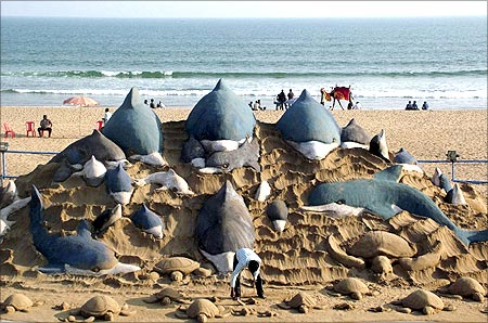 Sand artist Sudarshan Patnaik (C) gives finishing touches to his sand sculpture titled Nature and Environment in Orissa.