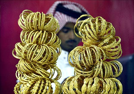 A goldsmith stands behind gold bracelets on display at his shop in Riyadh.