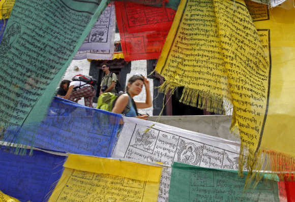 A French tourist walks past Buddhist religious flags at Namgyal Tsemo Gompa monastery in Leh.