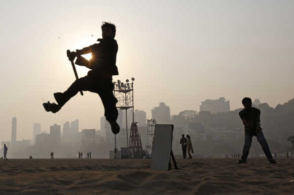 A man jumps in the air to hit a ball as people play cricket by the beach with an improvised stick for a bat and a piece of wood for wickets in Mumbai.