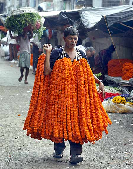 A vendor carries garlands of marigold flowers at a wholesale flower market in Kolkata.