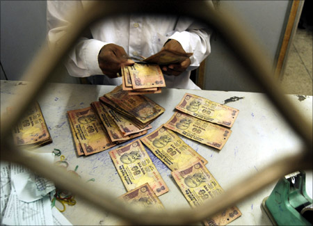 An employee sorts Indian currency notes at a cash counter inside a bank.