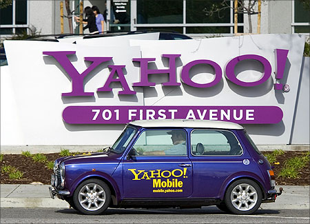 A man drives a Mini Cooper with a Yahoo! logo in front of Yahoo! headquarters in Sunnyvale, California.