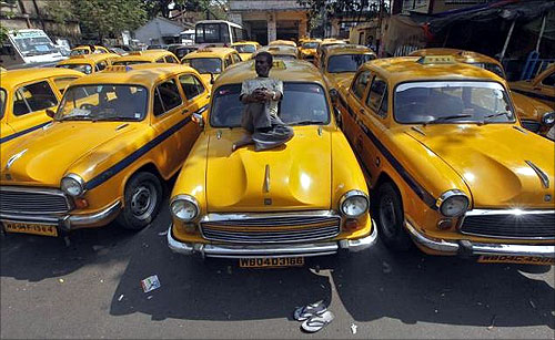 A driver rests on his iconic yellow ambassador taxi in Kolkata.