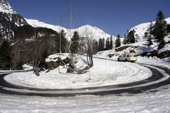 A truck moves on a road after it was cleared of snow near Gulaba village in Himachal Pradesh.