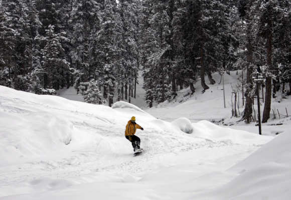 A man snow boards down a slope in Gulmarg, Jammu and Kashmir.