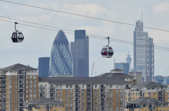Workers sit in gondolas as they perform tests on the new cable car link across the River Thames in London.