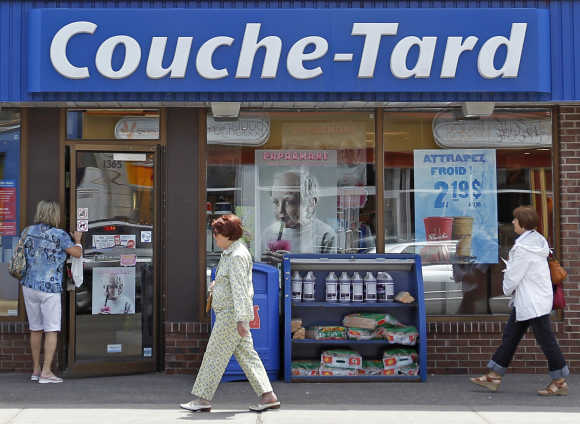 People walk past Couche-Tard store in Quebec City, Canada.