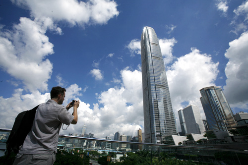 A visitor takes a picture in front of Two IFC, Hong Kong
