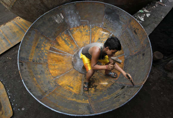 A boy checks the joints of a giant utensil at an iron utensils manufacturing unit in Kolkata.